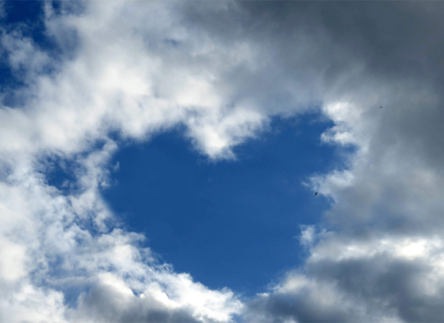 A view of the sky with clouds forming a heart shape