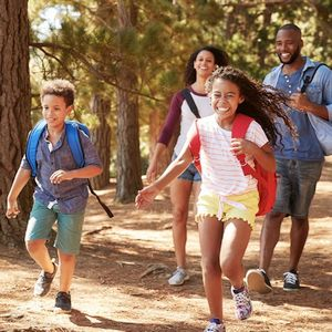 Young boy and girl happily running through the woods